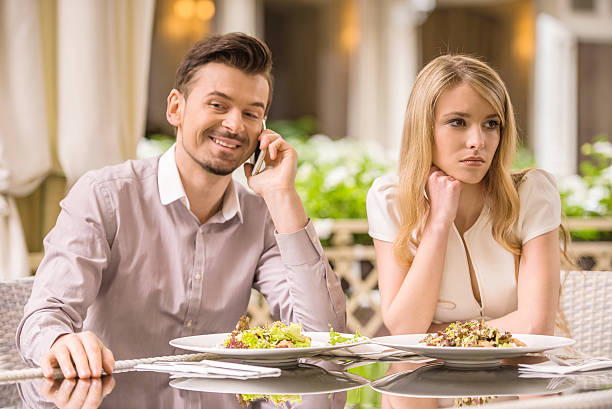 Romantic date Woman is getting bored in restaurant while her boyfriend is talking on the phone. bad date stock pictures, royalty-free photos & images