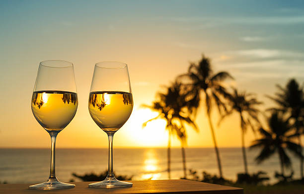 Romantic date Romantic glass of wine setting by the beach against a beautiful sunset. city break stock pictures, royalty-free photos & images