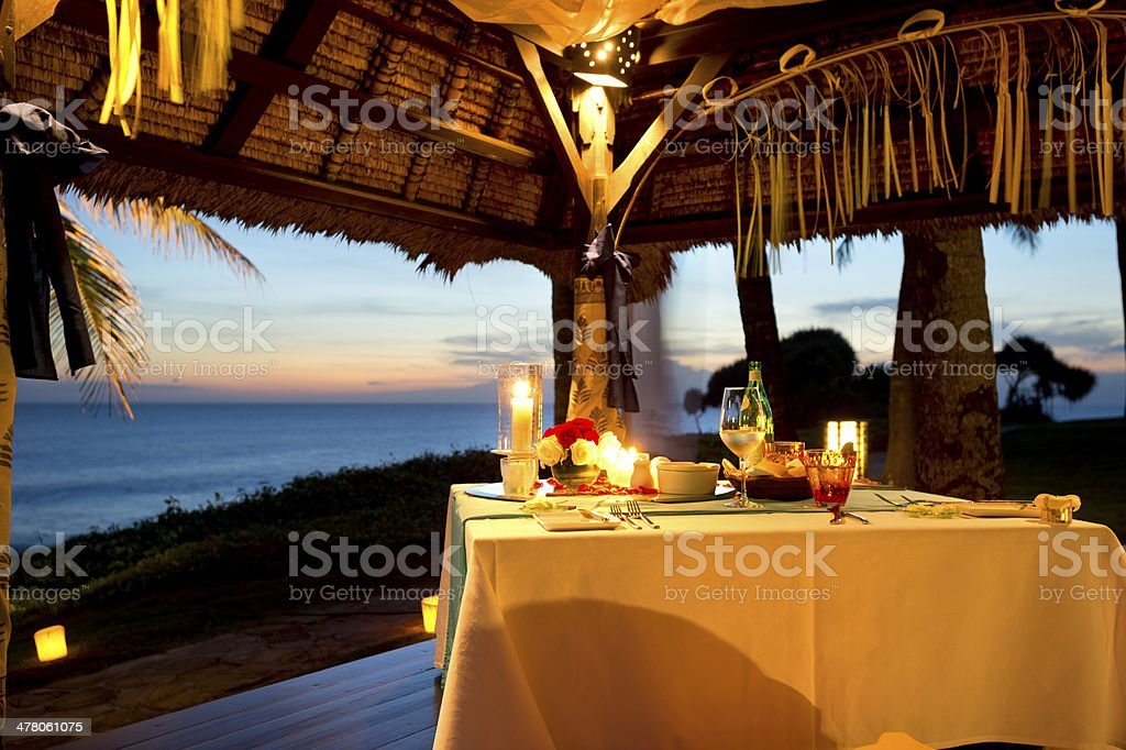 Romantic dinner by the sea at sunset stock photo