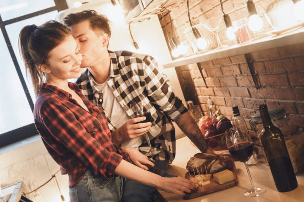 Romantic dinner concept. Cheeses and wine, husband kisses his wife stock photo