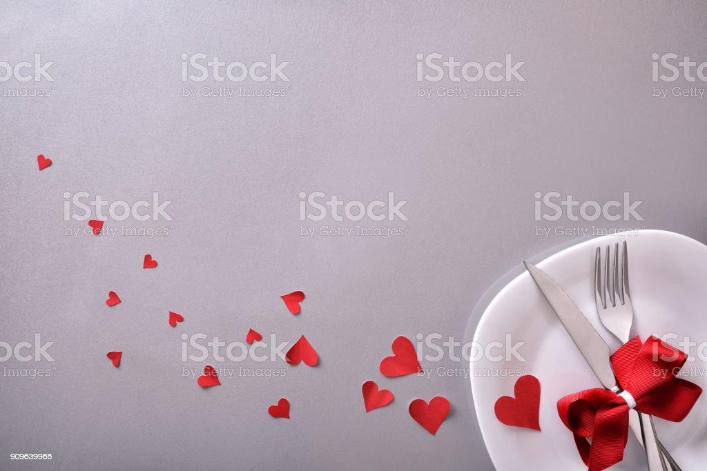 Cena romántica decoración con corazones rojos y fondo gris - foto de stock