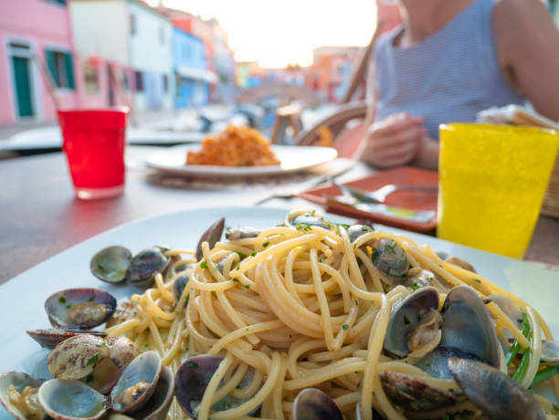 Romantic dinner for two in colorful town Burano, Venice, Italy. Italian Pasta Spaghetti with clams and spaghetti with seafood, Beautiful woman eats at a Restaurant Table along the canal near the boat stock photo