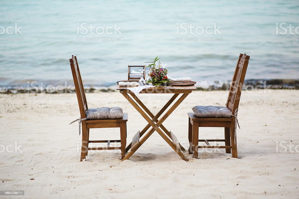 Romantic dinner for two served on a white sand beach royalty-free stock photo