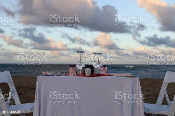 Table and chairs set up and decorated for the romantic dinner on the beach by the ocean. Dinner by the sea. Caribbean romantic dinner. Romantic evening in Dominican Republic. Sunset dinner by the sea.