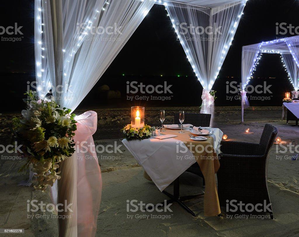 Romantic dinner setup on beach at night stock photo
