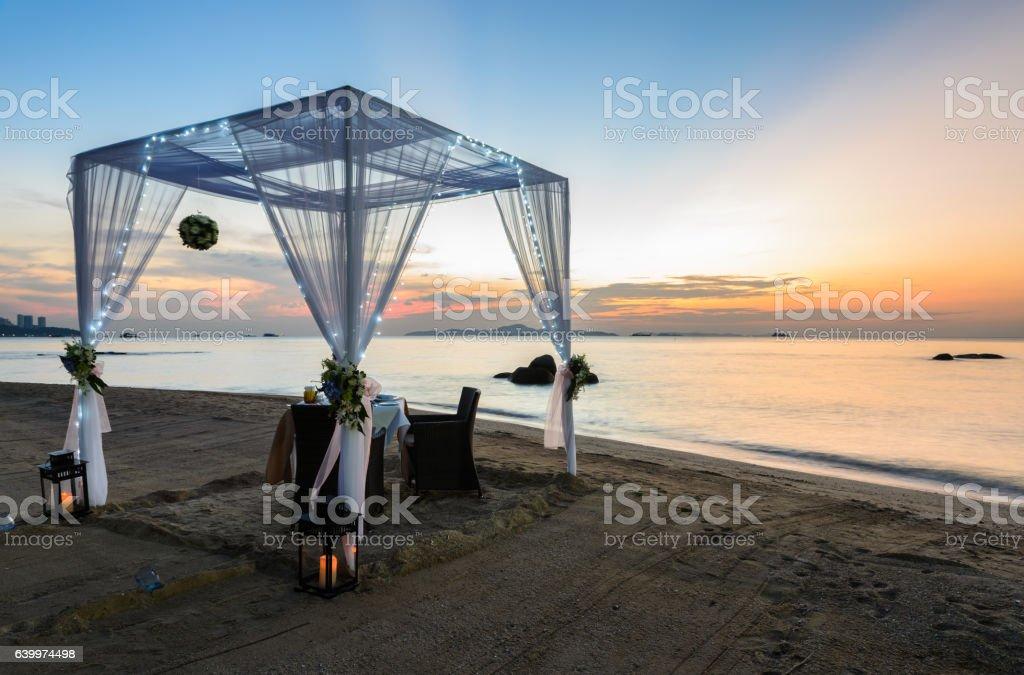 Romantic dinner setup on beach at sunset – Foto