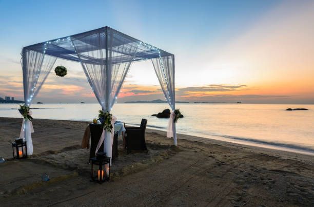 Romantic dinner setup on beach at sunset stock photo