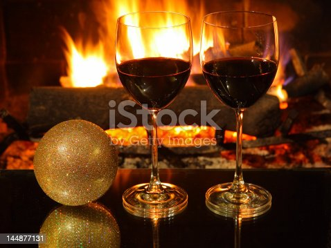 istock Romantic dinner, two glasses of red wine, fireplace, Christmas decoration. 144877131