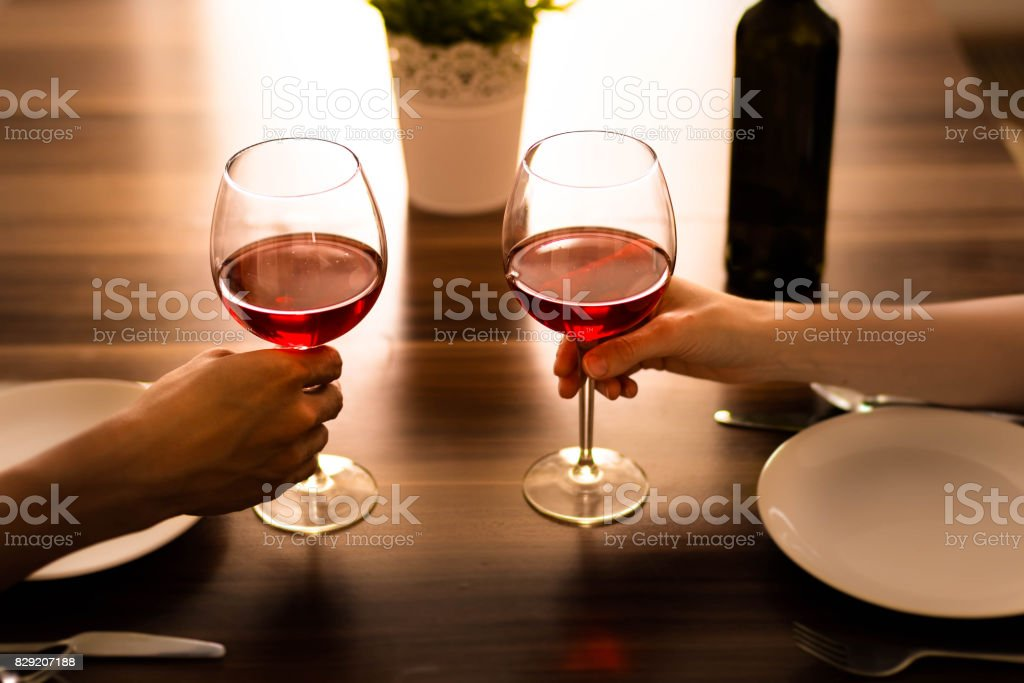 Romantic dinner. Two people each holding a glass of wine. stock photo