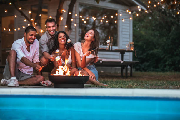 Romantic double dating by the pool Cropped shot of four handsome friends roasting marshmallows by the swimming pool backyard pool stock pictures, royalty-free photos & images