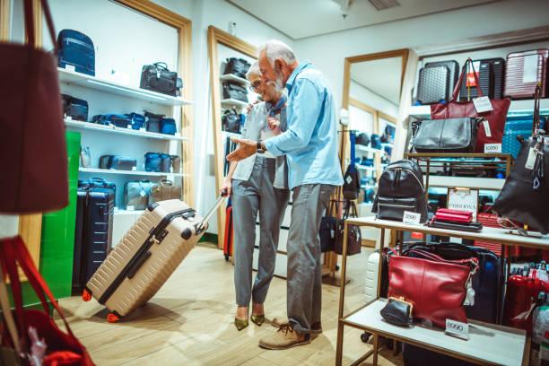 romantische älteres ehepaar wählen einen rechten rädern trolley-koffer in taschen und accessoires zu speichern - trolley kaufen stock-fotos und bilder