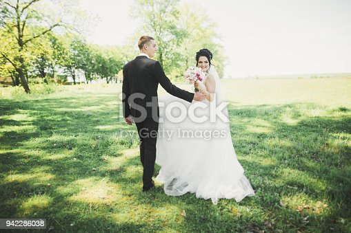 istock Romantic, fairytale, happy newlywed couple hugging and kissing in a park, trees in background 942286038