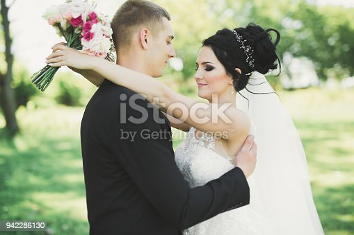 istock Romantic, fairytale, happy newlywed couple hugging and kissing in a park, trees in background 942286130