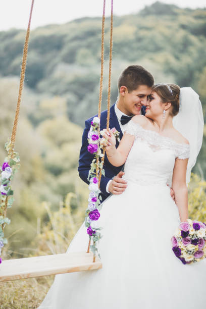 Romantic, fairytale, happy newlywed couple hugging and kissing in a park, trees in background stock photo
