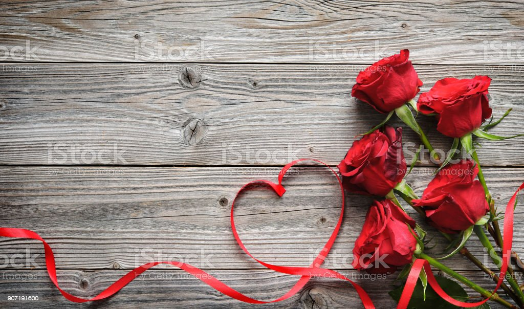 Romantic floral frame with red roses and ribbon on wooden background royalty-free stock photo
