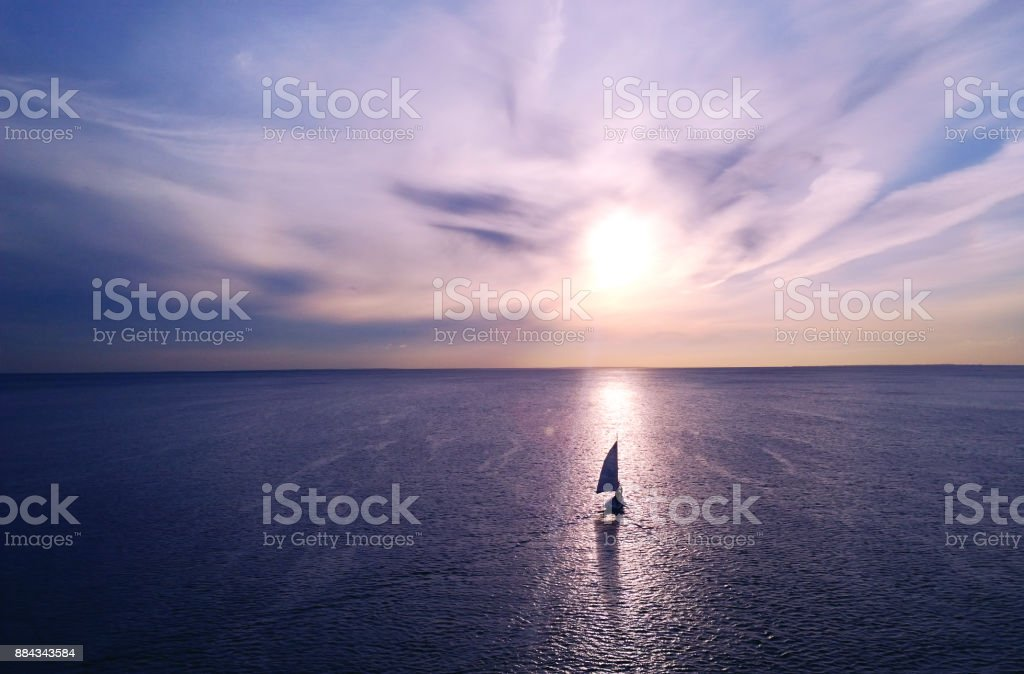 Romantic frame: yacht floating away into the distance towards the horizon in the rays of the setting sun. Purple-pink sunset - foto stock