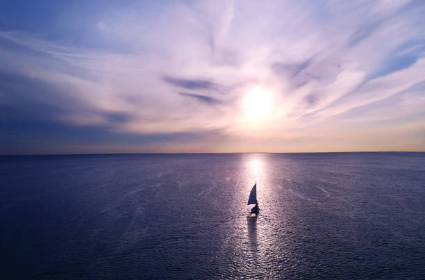 Romantic frame: yacht floating away into the distance towards the horizon in the rays of the setting sun. Purple-pink sunset stock photo