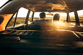 Rear view of embracing couple inside of car, enjoying on the road trip on sunset, photo is taken in car from 1980 year