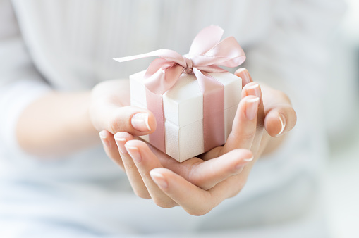 Close up shot of female hands holding a small gift wrapped with pink ribbon. Small gift in the hands of a woman indoor. Shallow depth of field with focus on the little box.