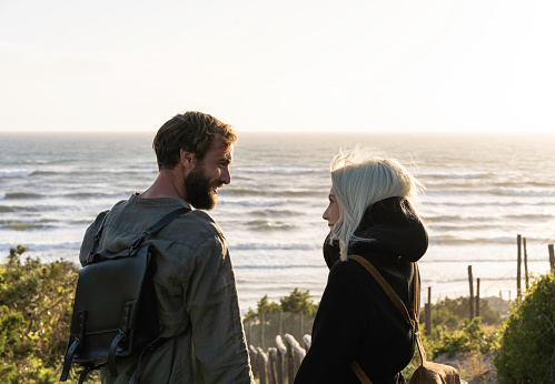 Romantic happy couple in love standing on wooden stairs on dunes at the wild beach in front of the sea - Boyfriend and girlfriend wearing vintage backpack looking into each other's eyes at sunset