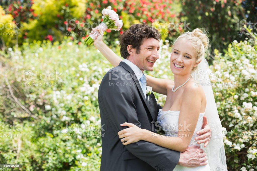 Romantic happy newlyweds embracing each other stock photo