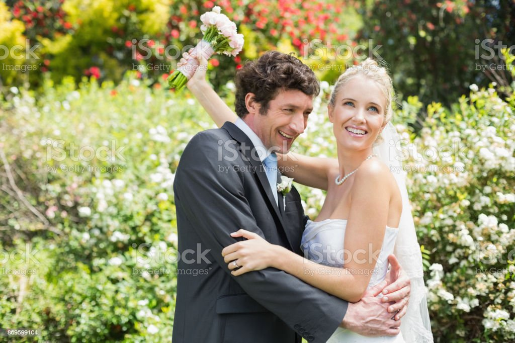 Romantic happy newlyweds hugging each other stock photo