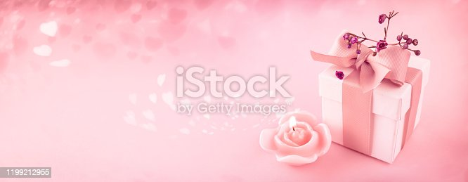 Floating hearts with gift box and scented candle on pink background. Romantic love concept for mother's day, valentine's day and wedding. Space for text and design.