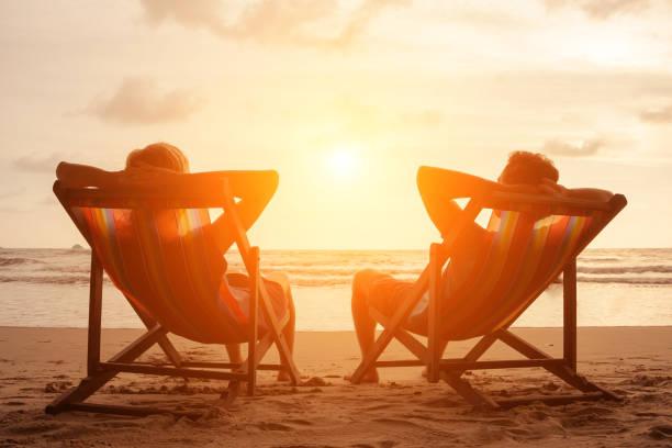 romantik tatil seyahat. mutlu genç çift güverte sandalyeleri lüks beach otel denize sıfır gün batımında oturan silüeti. aşk ve ilişki kavramı. tropik cennet adası yaz tatili. - emeklilik stok fotoğraflar ve resimler