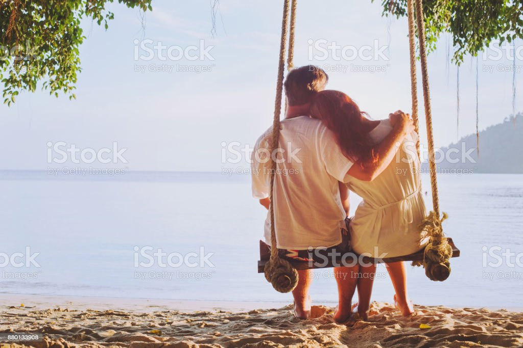 romantic holidays, honeymoon, affectionate couple on beach on swing stock photo