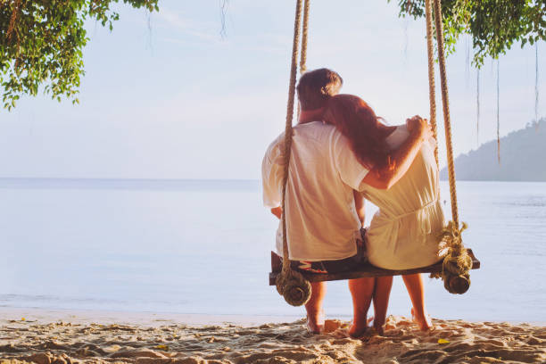 romantic holidays, honeymoon, affectionate couple on beach on swing - love stock photos and pictures