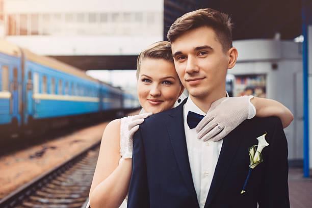 romantischen umarmung für brautpaar und trainiere in den hintergrund - festzugskleidung stock-fotos und bilder