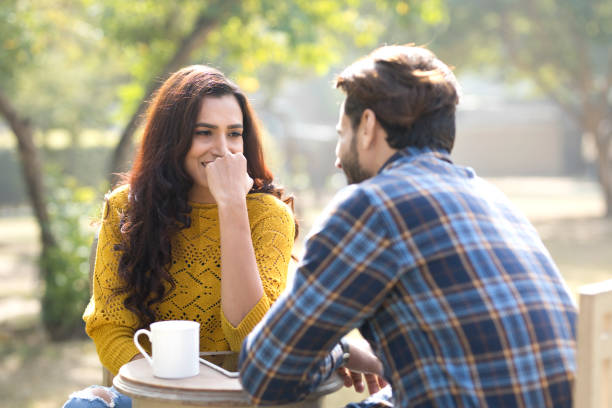 Romantic Indian couple having coffee at park Happy young couple with digital tablet and coffee cup at park romance stock pictures, royalty-free photos & images