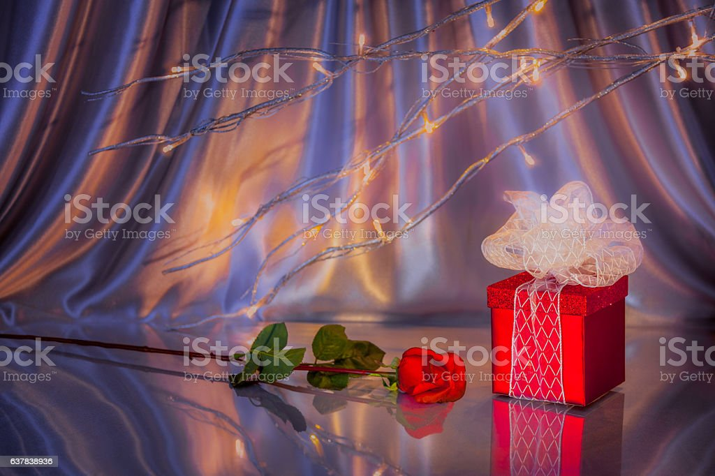 Romantic lights, red rose and gift are all reflected (P) stock photo