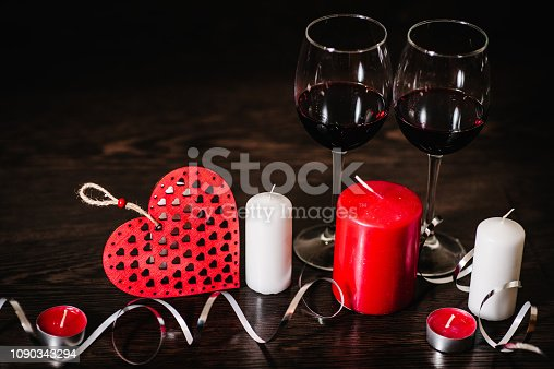 istock A romantic love concept holiday, candles, ribbons, wine, red hearts on brown wooden background. Place for text. concept Women's Day, eighth of March. Wedding, jubilee. St. Valentine's Day. 1090343294