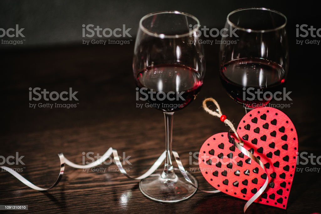 A romantic love concept holiday, ribbons, glasses of wine, red hearts...