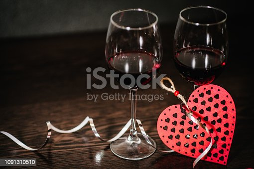istock A romantic love concept holiday, ribbons, glasses of wine, red hearts on brown wooden background with space. Place for text. Women's Day, eighth of March. Wedding. St. Valentine's Day. 1091310510