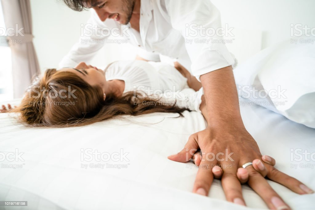 Romantic love of young couple in the bedroom. stock photo