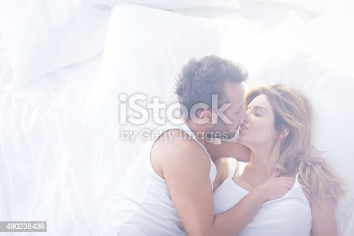 istock Romantic lovers kissing in bed 490238436