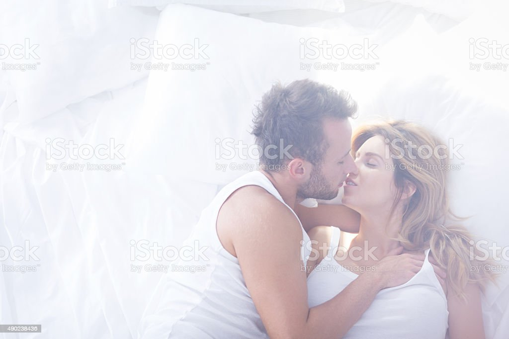 Romantic lovers kissing in bed stock photo