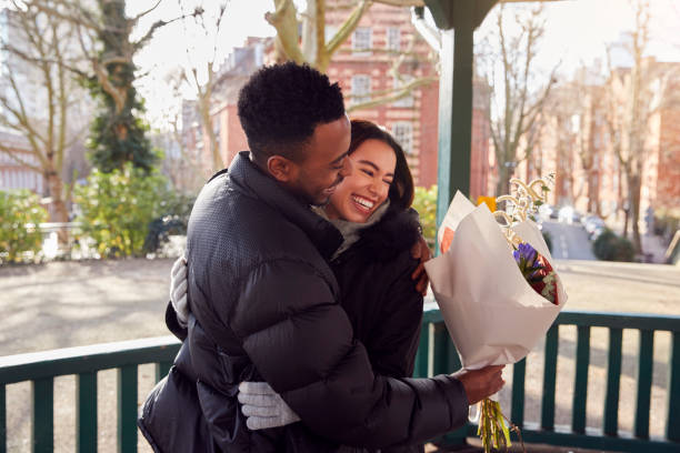 Romantic Man Hugging Young Woman After Giving Her Bouquet Of Flowers As They Meet In City Park stock photo