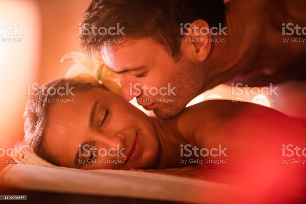 Young loving man kissing his girlfriend in the cheek at the spa.