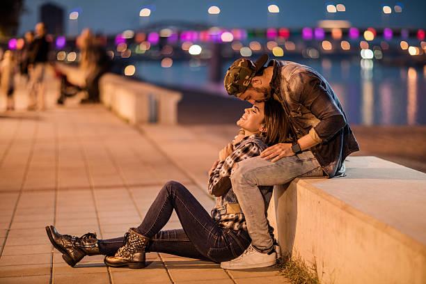 Romantique homme embrasser Sa petite amie sur le front de la rivière. - Photo