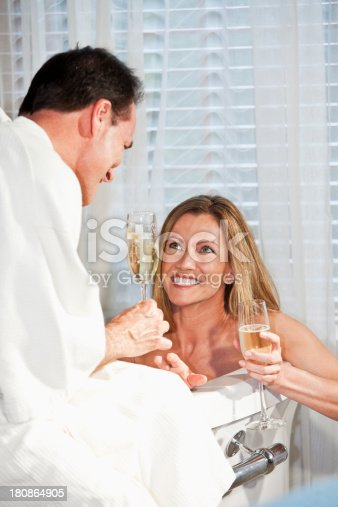 610769340istockphoto Romantic mature couple with champagne in bathtub 180864905