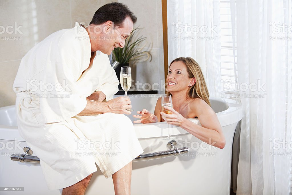 Romantic mature couple with champagne in bathtub stock photo
