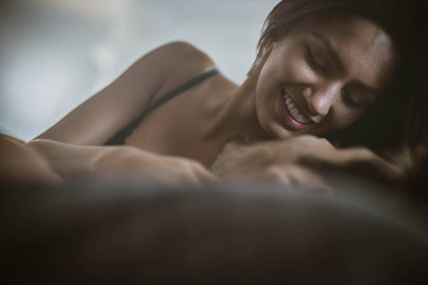 Romantic moment in bed! Happy woman in underwear talking to her boyfriend on a bed in bedroom. real couples making love stock pictures, royalty-free photos & images