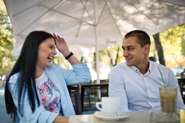 momentos románticos de pareja joven sentado en una cafetería y tomando café, al aire libre. - happy couple sharing a cup of coffee fotografías e imágenes de stock