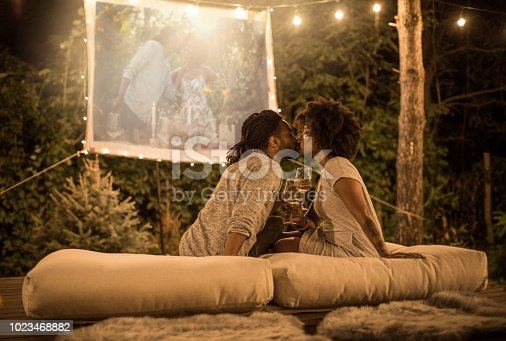 Romantic couple sitting at backyard and looking movie at home improved theater. Backyard is decorated with string lights.