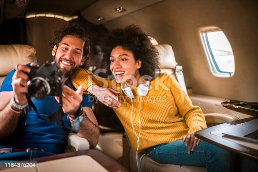 Romantic diverse couple looking at photos on a camera together while traveling aboard a private airplane.