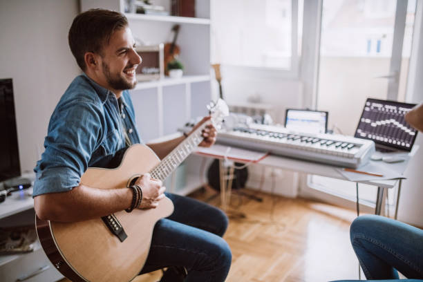 Romantic Musician Playing Acoustic Guitar At Home stock photo