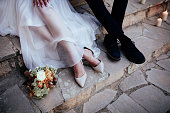 Close-up of bride and groom with flower bouquet sitting together on stone staircase outdoors